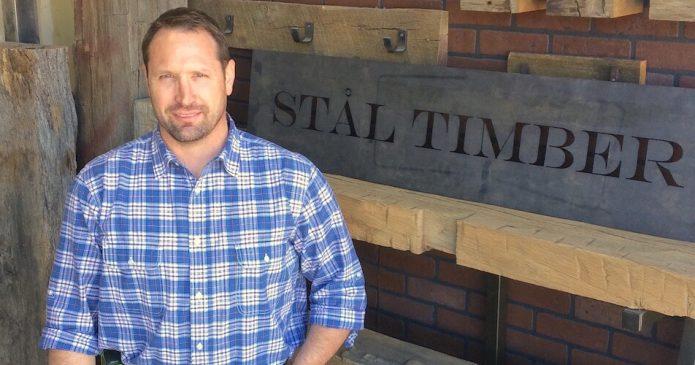 Josh Marten standing in front of the Stal Timber sign